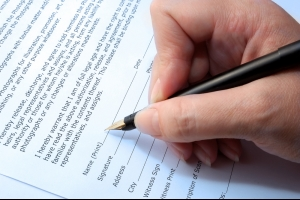 Close up of a person completing a contract.